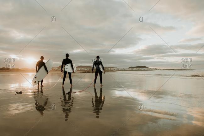 People with surfboard walking near sea