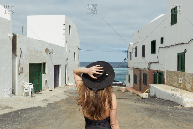Back view of stylish woman touching hat while standing on shabby street of small coastal town on cloudy day near sea