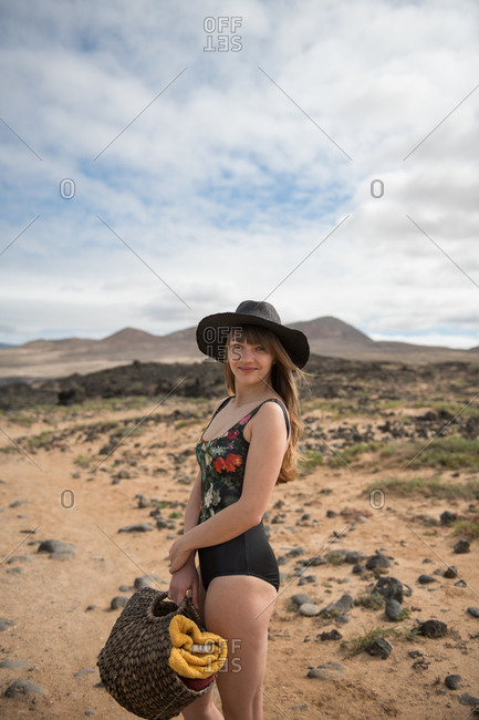 Side view of charming young lady in stylish swimsuit and hat holding bag with towels and looking at camera while standing in amazing countryside on cloudy day and smiling