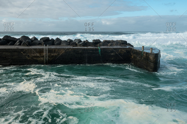 Breathtaking view of amazing stormy sea waving near weathered stony pier on cloudy day