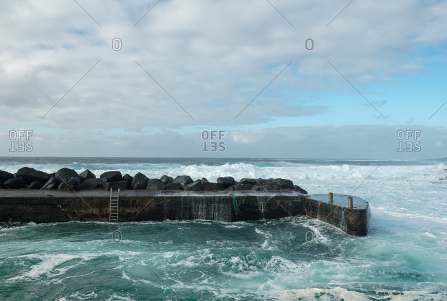 Sea waving near stone pier