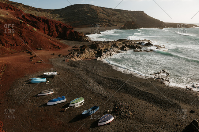 Modern boats located on rocky coast near waving sea and amazing hills on sunny day in wonderful countryside
