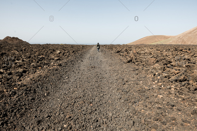 Back view of tourist walking on rocky countryside road against cloudless sky in beautiful nature