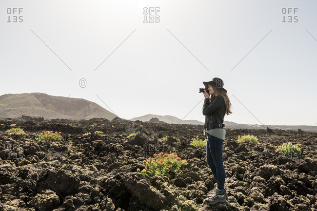 Side view of female in casual outfit using photo camera to take pictures of wonderful stony terrain on sunny day