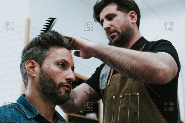 From below barber combing hair of handsome stylish male sitting in barbershop