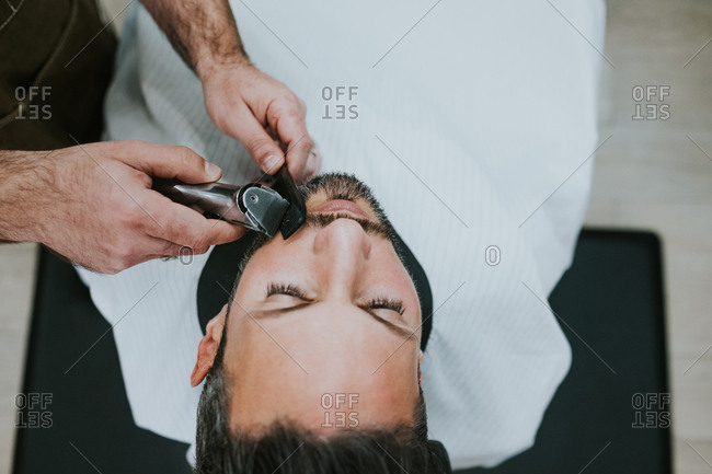 Closeup crop hands of barber with comb and trimmer cutting beard of male sitting in barbershop on blurred background
