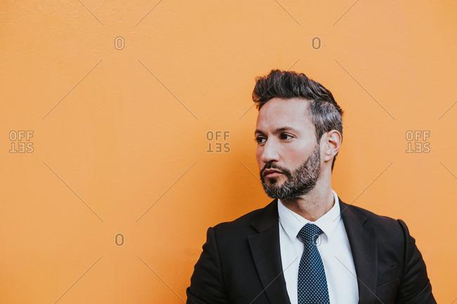 Adult handsome elegant businessman in formal suit adjusting jacket and looking away near orange wall
