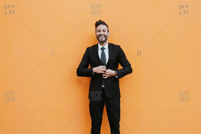Adult handsome elegant businessman in formal suit adjusting jacket and looking at camera near orange wall