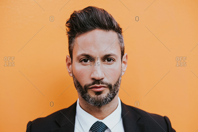 Adult handsome elegant businessman in formal suit looking at camera near orange wall