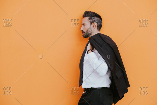 Side view of adult handsome elegant cheerful businessman in formal suit with hand in pocket looking away near orange wall on city street
