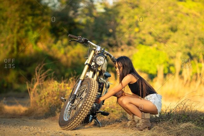 Woman fixing motorbike in countryside