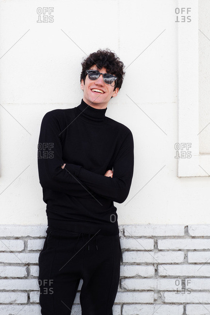 Young slim brunette guy in black cloths posing near building on street in sunny day
