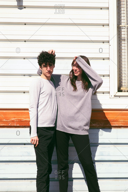 Young slim brunette guy and woman in stylish cloths posing near building on street in sunny day
