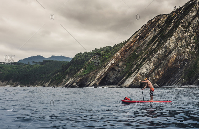 Adult male standing on paddleboard and rowing with paddle on surface of rippled sea water against gray cloudy sky