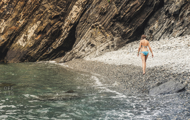 Back view of adult female in swimwear walking on stony shore and waving sea