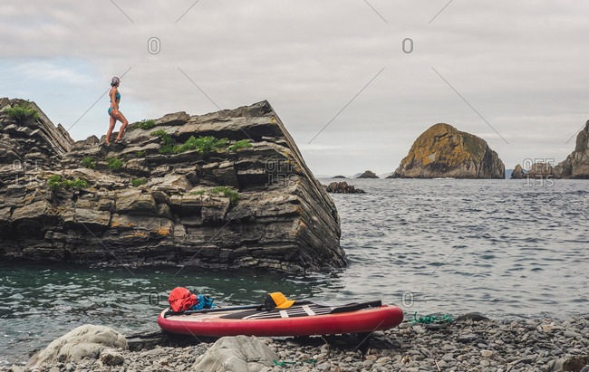 Side view of adult female in swimwear standing on rough cliff near red paddle board and waving sea in a stony shore