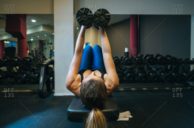 Woman lifting dumbbells on bench