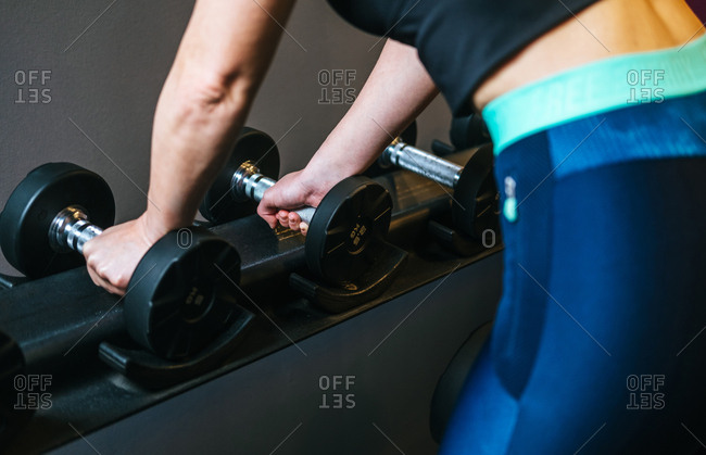 Woman taking dumbbell in gym