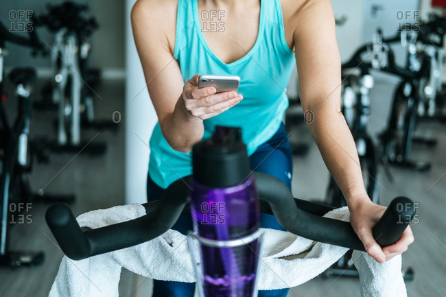 Woman with smartphone and towel and water on exercise machine