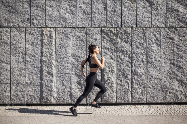 beautiful and brunette woman running on a sunny morning with a granite wall in the background