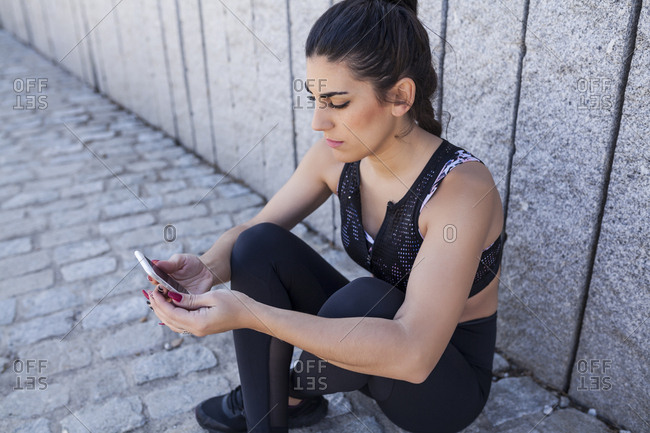 beautiful and brunette woman sit down and looking at the statistics of the training app