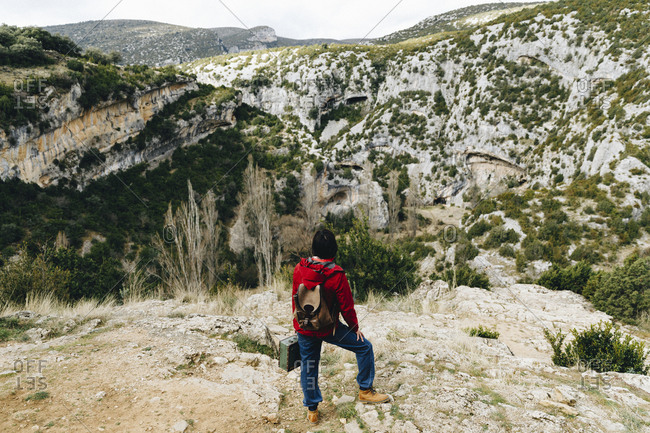 Back view of traveling woman with backpack sitting on high rocky cliff observing beautiful valley