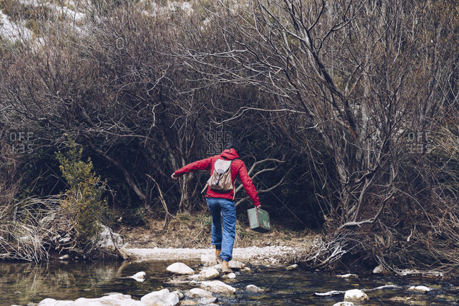 back view of casual woman carrying case and jumping on rocks of clear stream of water in nature