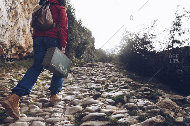 back view of casual woman carrying case and walking on rocks of clear stream of water in nature