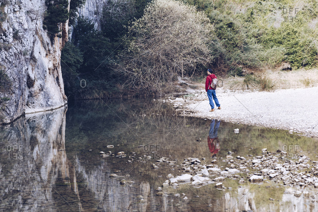 Back view of male with backpack on coast of mountain river near rock mountain