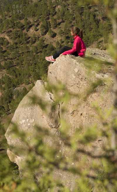 Side view of young girl in sportswear admiring view of wonderful countryside while sitting on rocky cliff in nature