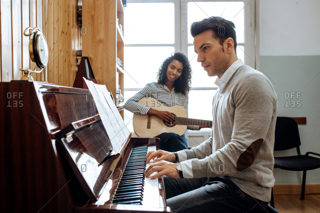 Side view of young man playing piano near black woman playing guitar in music studio