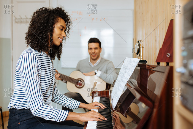 Side view of young black woman playing piano near man playing guitar in music studio