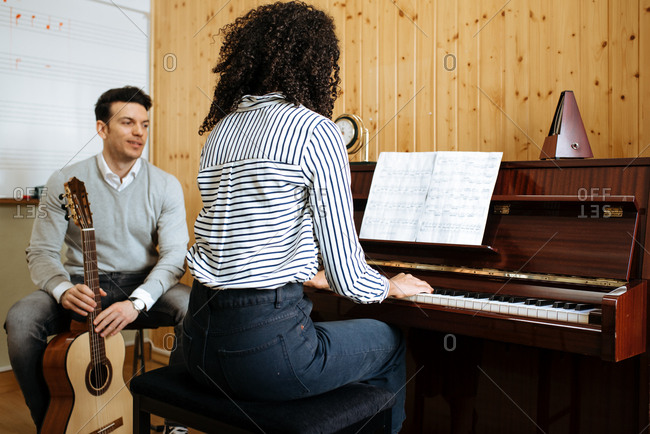 Back view of young black woman playing piano near man playing guitar in music studio