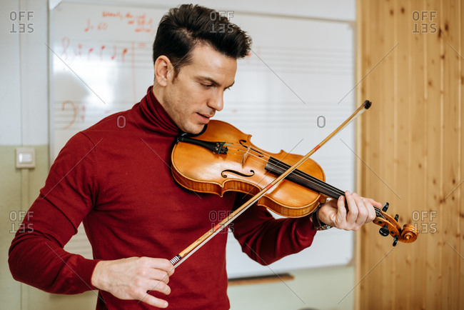 Young man playing violin with writing board on the background in music studio