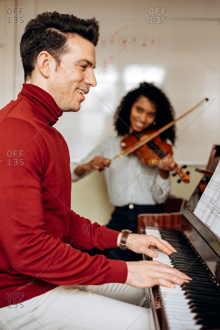 Side view of young man playing piano near black woman playing violin in music studio