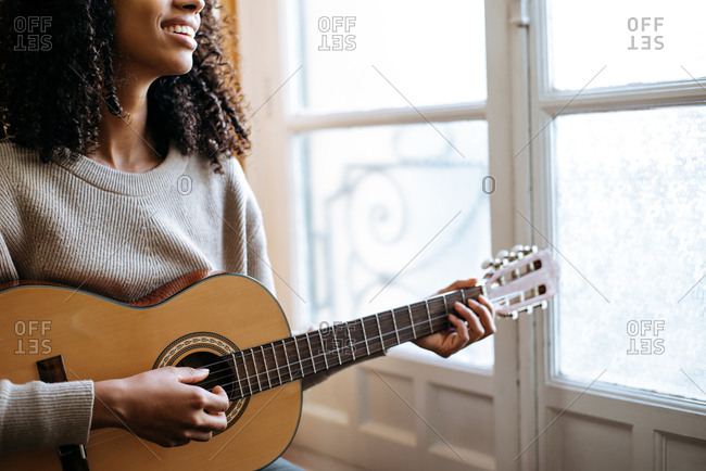 Black woman playing guitar during rehearsal in recording studio.
