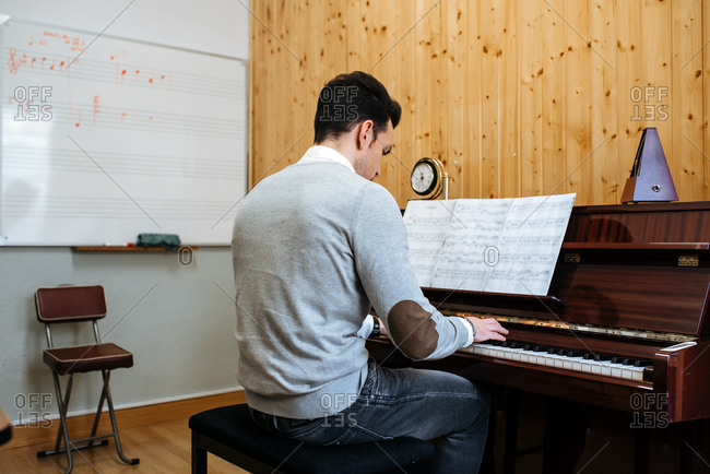 Back view of a handsome man playing piano during rehearsal in recording studio.