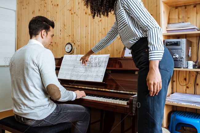 Young man learning to play piano near black woman teaching in music studio