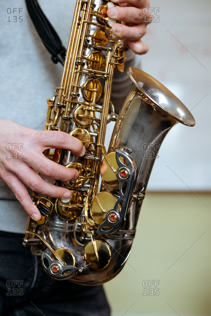 Cropped unrecognizable man playing saxophone in studio