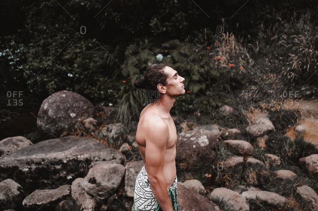 Side view of handsome shirtless male keeping eyes closed and enjoying weather while standing near rough stones and bushes in countryside