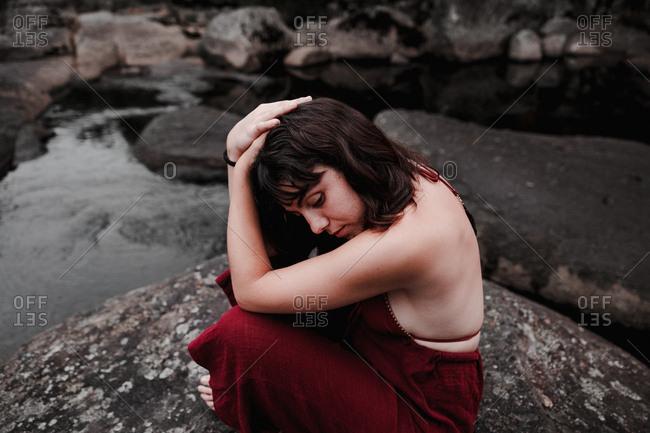 Woman sitting on stones near waterfall