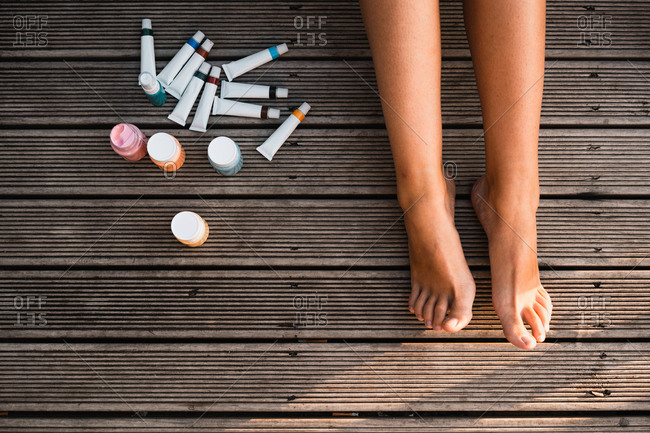 From above legs of anonymous barefoot artist lying on lumber terrace near bottles and tubes of paint on sunny day
