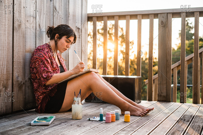 Side view of attractive barefoot female painting in notebook while sitting on terrace of wooden house on sunny day