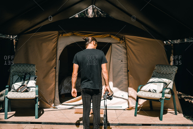 Back view of young photographer standing near chairs and enter of tent with bed