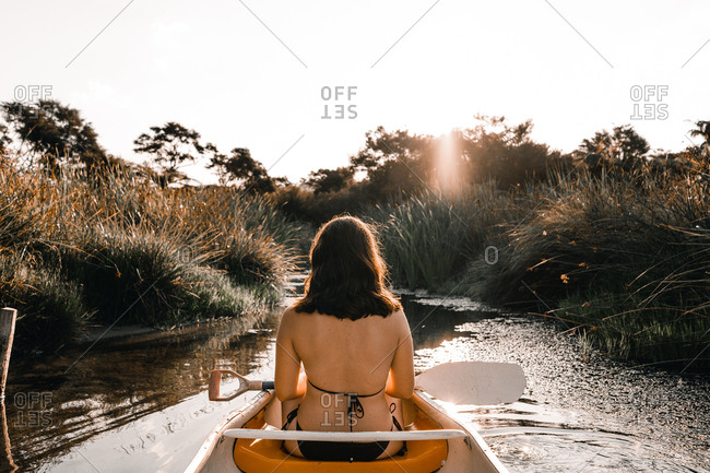 Back view of young woman with paddle in boat floating between water surface near coast with green trees