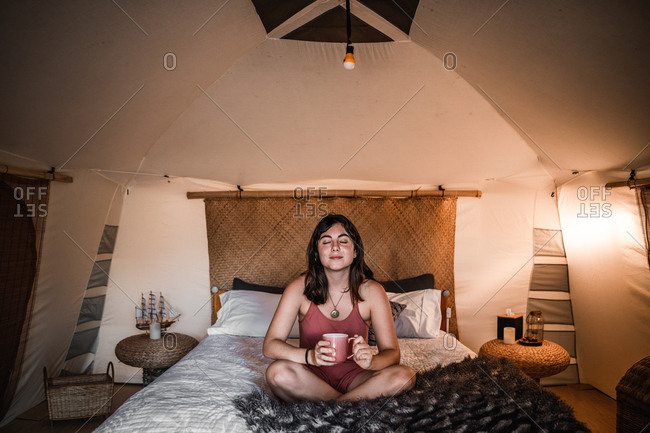 Young woman with closed eyes holding cup and sitting on comfortable bed in tent