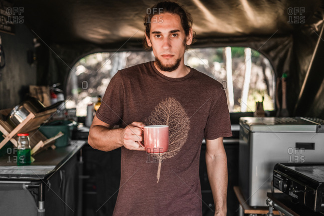 Young serious man holding mug between camp kitchen in tent