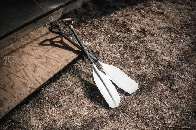 From above paddles placed near wooden board on land with dry grass