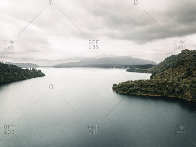 From above picturesque view of water surface near shores with green trees and cloudy heaven
