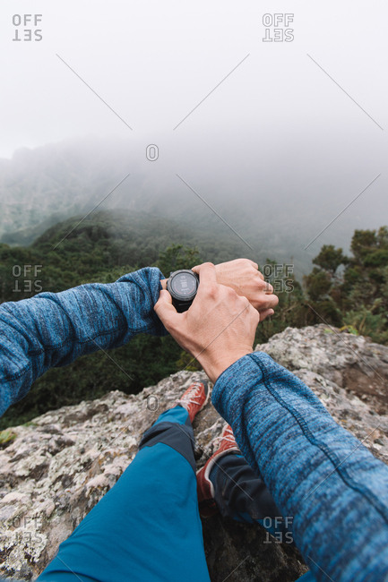 First person view of a crop hand of guy using a watch in the mountains